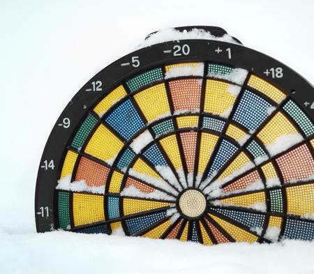unpredictable: Dartboard thermometer in the snow - unpredictable weather concept, outdoor shot