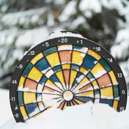 weather gauge: Dartboard thermometer in the snow - unpredictable weather concept, outdoor close up with blurred forest in the background