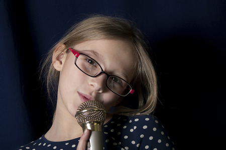 10 fingers: Young female singer with a tilted head holding microphone,  curtain in the background, studio shot