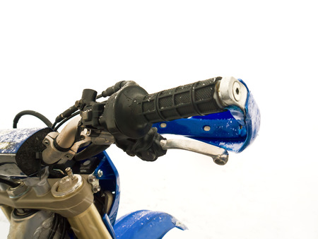 particular: Close up of a motorcycle throttle control and handlebar in snow, outdoor shot with particular focus