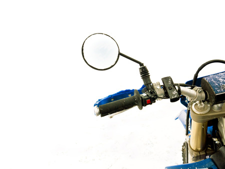 handlebars: Close up of a motorcycle handlebar with mirror, outdoor shot