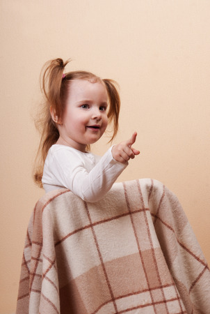 only 3 people: Portrait of a little blond girl sitting on a chair covered by plaid and pointing by finger Stock Photo