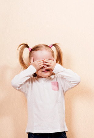 Little girl with ponytails playing peek a boo, indoor vertical shot Stock Photo