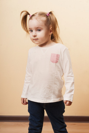 ponytails: Vertical portrait of a looking serious 3 years old girl with ponytails Stock Photo