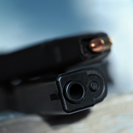 gun barrel: Close up of a hand gun barrel with muzzle and loaded magazine in the blurred background Stock Photo