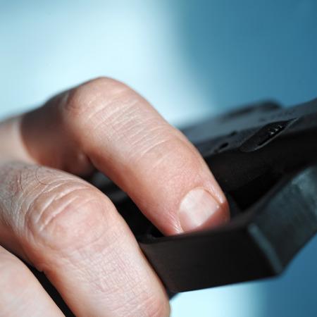 gatillo: Primer plano de una mano masculina tirando de un gatillo de la pistola, tiro con someras DOF