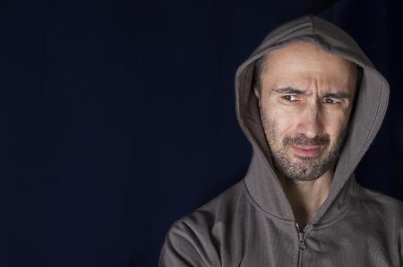 distrustful: Portrait of distrustful unshaven man in hood, horizontal studio shot