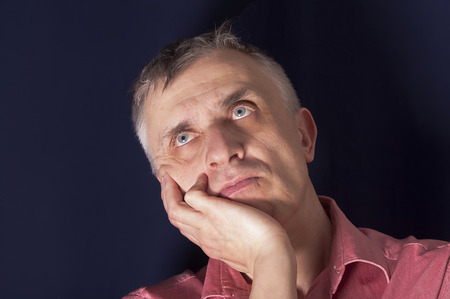 apathetic: Studio portrait of a man in melancholy, looking up and holding his head Stock Photo
