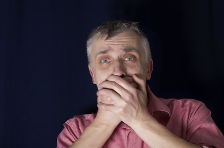 stunned: Studio portrait of a stunned man, covering his mouth by his own hands