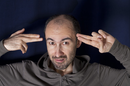 own: Studio portrait of a bizarre man, pointing hand gun at his own head