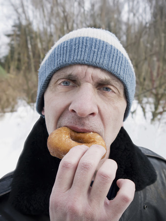 matured: Hungry matured man biting donut, outdoor vertical shot with blurred background Stock Photo