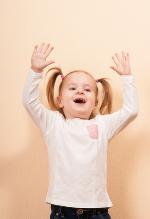 tilted: Studio portrait of an absolutely happy little girl with the hands up and tilted head