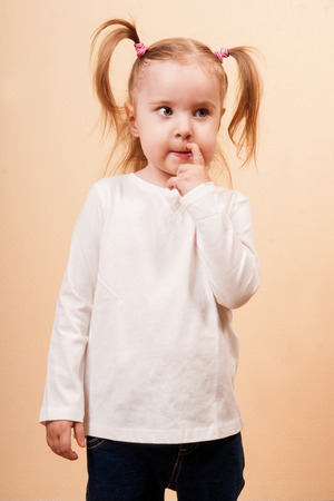 Thoughtful little girl with funny pony tails, vertical studio shot photo