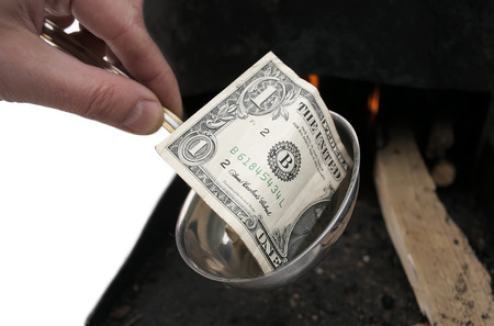 burning money: Dollar bill instead of soup in ladle, food prices increasing concept, isolated on white
