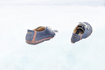 beyond: A pair of shoes walking on snow without man, concept of beyond belief