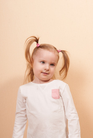 only 3 people: Portrait of a little girl listening attentively, vertical studio shot