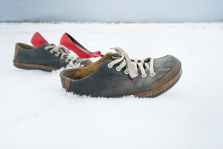 without people: Men and ladies shoes walking on snow without people, concept of beyond belief