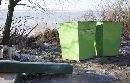 overflowing: Two overflowing rubbish bins on a shore lake after winter, outdoor shot