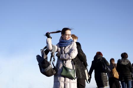 tail woman: Presentaci�n de la mujer joven, sosteniendo su cola de caballo, grupo de turistas Fmale en el fondo, bajo el �ngulo de disparo al aire libre contra un cielo azul