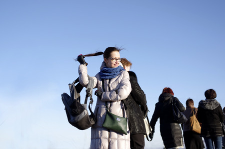 fmale: Young woman posing, holding her pony tail, group of fmale tourists in the background, low angle outdoor shot against a blue sky