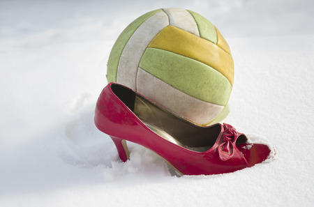 side shot: Side shot of a football ball and red high heel on the snow, concept of sport and fashion