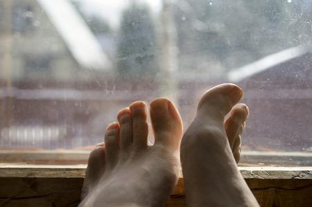 tembellik: Bir pencere pervazına bir erkek çıplak ayak çekim, tembellik kavramı, hiçbir şey ve tefekkür yapıyor
