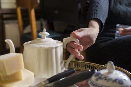 indoor shot: Female hand holding teapot handle, indoor shot with selective focus