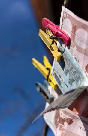 european currency: European currency banknotes pinned on a rope, vertical outdoor shot with a shallow depth of field