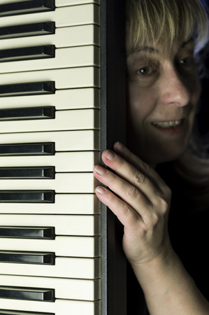 indoor shot: Portrait of a laughing woman with a keyboard, indoor shot with particular focus