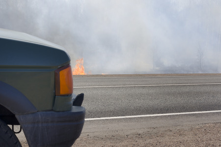 abandoned car: Abandoned car in the foreground, fire and smoke in the background, concept of war or natural disaster. Stock Photo