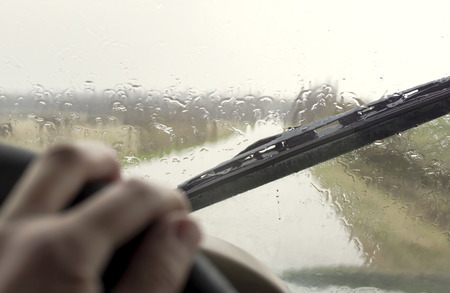 windscreen wiper: Driving through the rain and storm, focus on the wiper and windscreen
