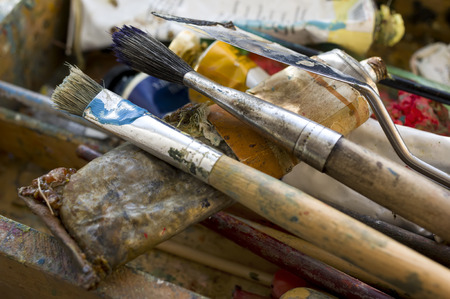 differential focus: Painting brushes in a splattered artist box,  differential focus horizontal shot
