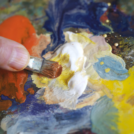 color mixing: Artist hand with a painting brush mixing color on the palette, indoor square shot
