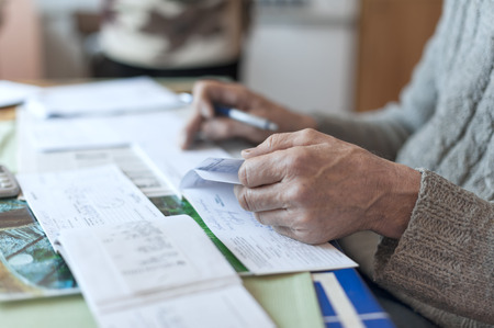 indoor shot: Male hand doing some paperwork, indoor shot with a shallow depth of field