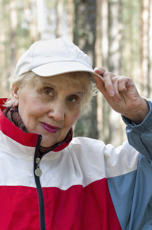 70 75 years: Senior female in a sport wear posing outdoors Stock Photo