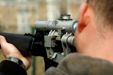 identifiable: Looking down the barrel of a russian sniper rifle being held by a non identifiable man dressed in casual wear Stock Photo
