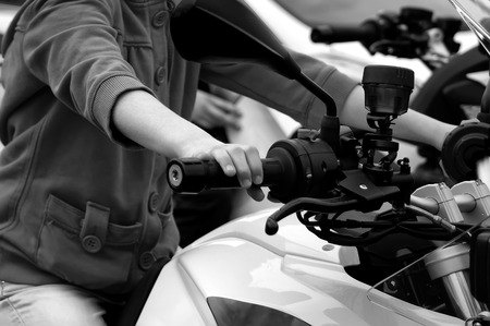 throttle: Driving motorcycle, child hand on a throttle control, horizontal black and white image