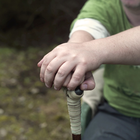 yard stick: Male hands leaning on a walker stick backyard in the blurred background outdoor square shot Stock Photo