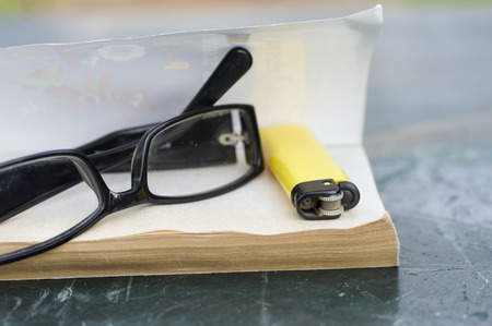freetime: Glasses and lighter on open book concept of freetime shot with shallow depth of field Stock Photo