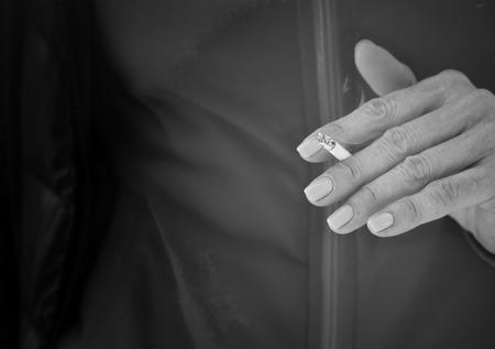 malos habitos: Manos femeninas con la manicura concepto de retenci�n del cigarrillo de los malos h�bitos en blanco y negro Foto de archivo