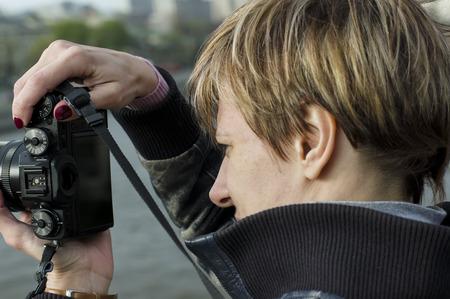 Female photographer focusing her photo camera outdoor horizontal shot