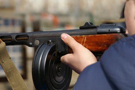 automatic machine: A man pointing a retro automatic machine gun outdoor horizontal shot