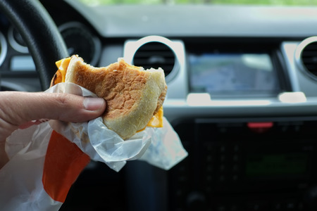 Closeup of a hand with a snack wrapped in a paper concept of driving and eating