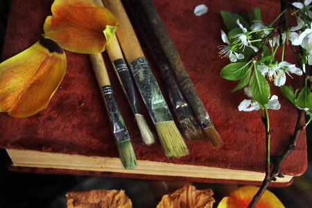 fine arts: Artist brushes and flowers on a retro book concept of fine arts Stock Photo