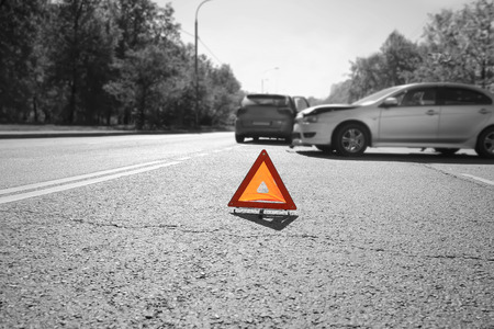 white car: Hazard warning triangle laid out on the road  behind two crashed cars black and white photo with a  red accent on a triangle Stock Photo
