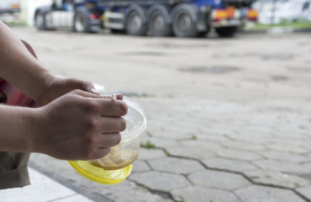 truck driver: Hands of a driver holding a plastic container with soup, truck in the blurred background