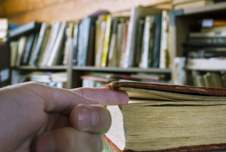 indoor shot: Old book and a male hand holding the fingers as a book tab, indoor shot with selective focus