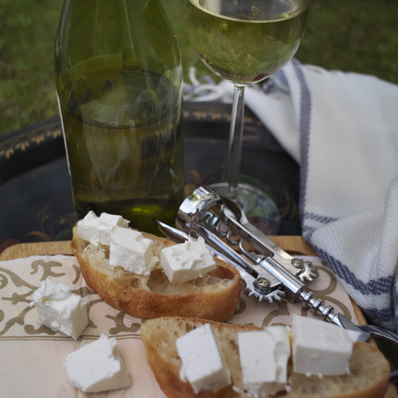 picnicking: Glass and bottle of white wine in the blurred background, bread with cheese in focus Stock Photo