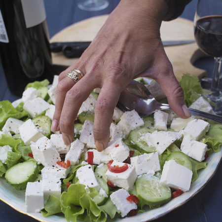 grabbing: Closeup of a female hand, grabbing salad, wine bottles in the background Stock Photo