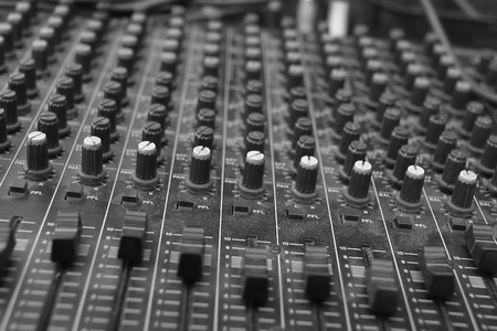 tweak: Close up of the rows of knobs and sliders on an analogue mixing console, in black and white